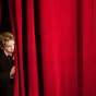 Boy on stage red curtain