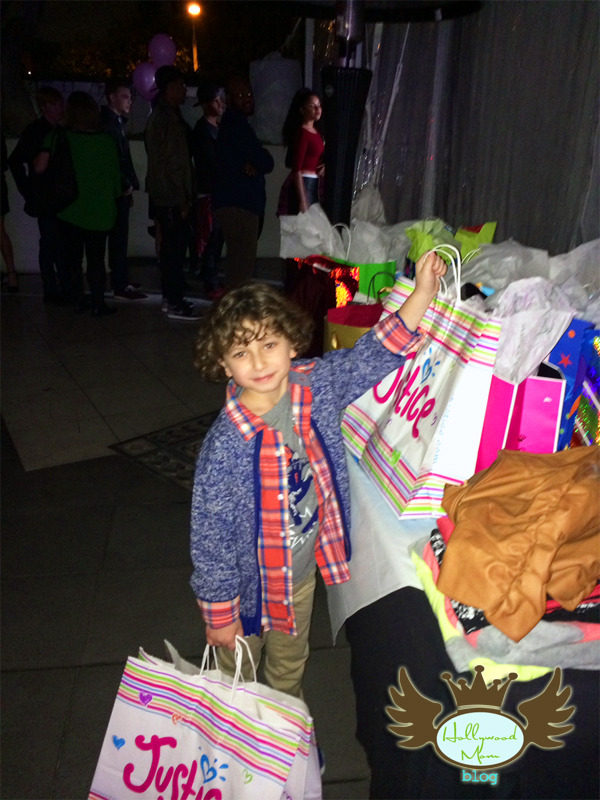 """In lieu of gifts, Guests like August Maturo bring clothing for the charity """"Threads for Teens"""""""